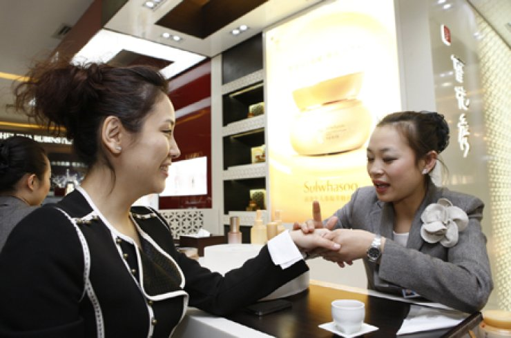 A consumer has a clerk apply a Sulwhasoo skincare product at Parkson Department Store in Beijing, China in this file photo. AmorePacific sees strong growth potential in the neighboring country thanks to the continued popularity of Korean beauty products. / Courtesy of AmorePacific