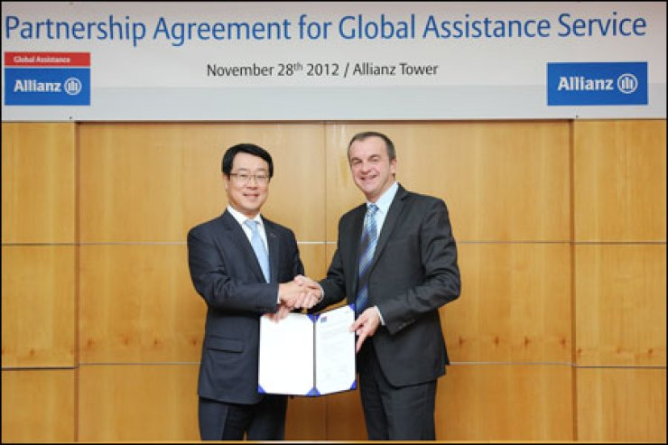 Allianz Life Korea CEO Cheong Mun-kuk, left, shakes hands with Christophe Aniel, Allianz Global Assistance's North Asia regional director, after signing a contract to cooperate in the global assistance service at Allianz Korea's head office in Seoul, Wednesday.                         / Courtesy of Allianz Life Korea