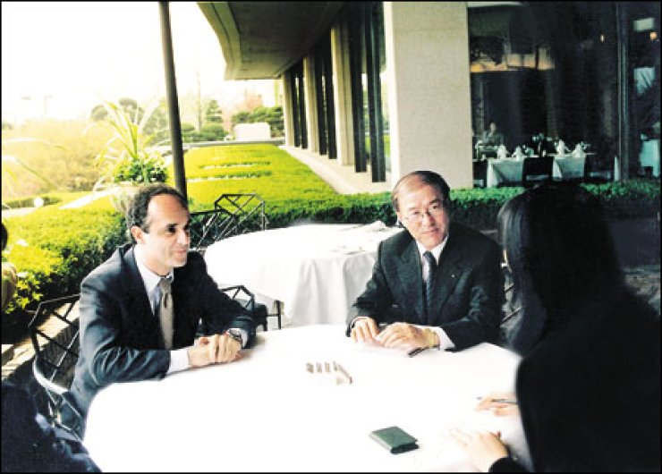Gene Yoon, center, sits next to Michele Scannavinim, left, the then CEO of Fila Holdings Italy in this undated photo.                                   / Korea Times file