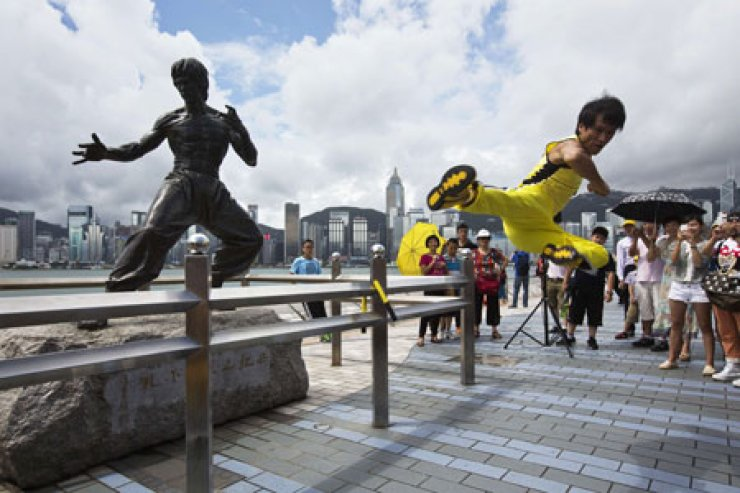 Chinese actor Mei Zhiyong performs a flying kick in front of a bronze statue of kung fu legend Bruce Lee on the waterfront of Hong Kong, Saturday. Fans are gathering in Hong Kong for a series of commemorative events to mark the 40th death anniversary of Lee, who starred in movies such as 'Enter The Dragon' and 'Game Of Death.' / AP-Yonhap
