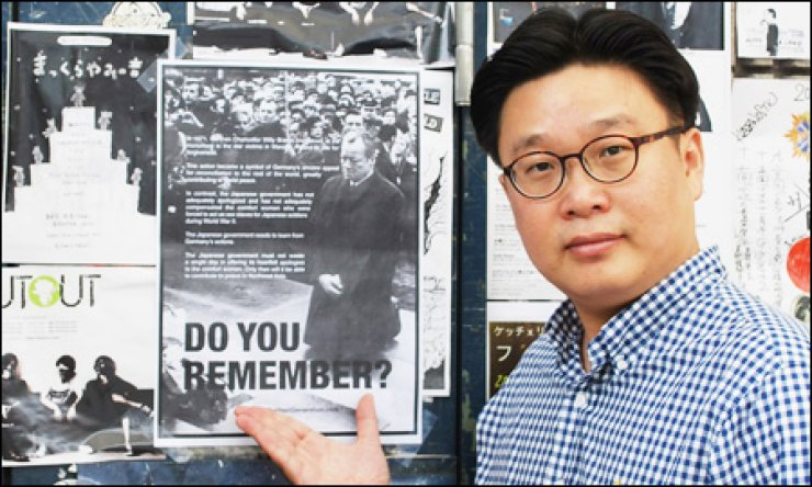 Korea PR expert Seo Kyoung-duk, a professor at Sungshin Women's University, poses in front of the comfort women posters he put up in Japanese universities, Monday. / Yonhap