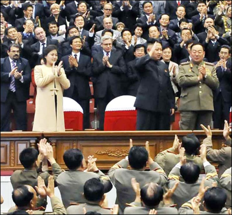 Ri Sol-ju, left in front row, applauds as her husband North Korean leader Kim Jong-un, to her left, reacts during a musical performance to mark the 60th anniversary of the founding of the Kim Il-sung Military University, in Pyongyang, Monday. / Yonhap