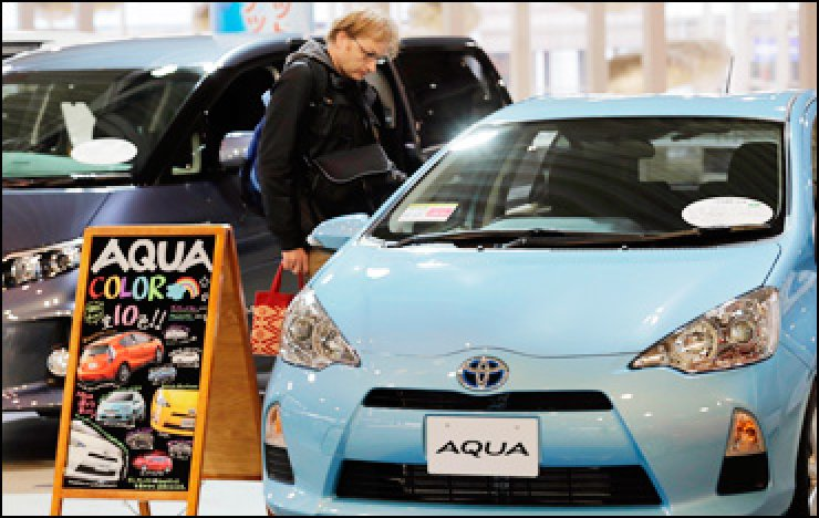 A man inspects an Aqua vehicle at a Toyota Motor showroom in Tokyo, Nov. 5. / AP-Yonhap