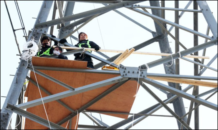 Three former employees of Ssangyong Motor, including Han Sang-kyun, ex-leader of the automaker's labor union, hold a sit-in on a 50-meter electrical supply tower near the company's plant in Pyeongtaek, Gyeonggi Province, Tuesday. / Yonhap