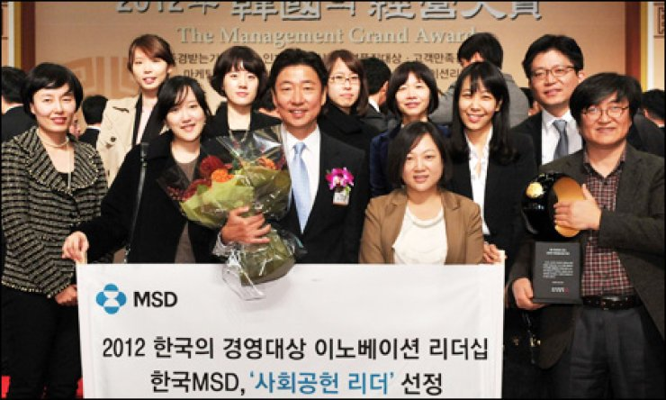 MSD Korea President Don Hyun, center in the front row, holds a bouquet of flowers along with the company's employees after getting a prize for corporate social responsibility activities from the Korea Management Association Consulting this month at the Grand Hilton Seoul.                                                                                                     / Courtesy of MSD Korea