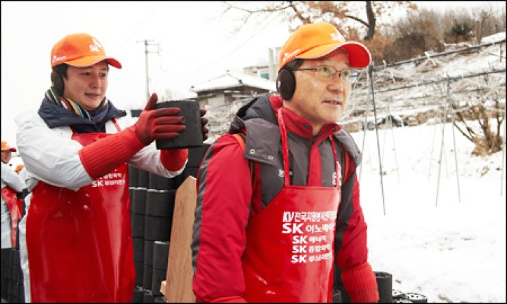 SK Innovation CEO Koo Ja-young, right, delivers coal briquettes to low-income households in central Seoul with employees on Dec. 7.                                                                                                        / Courtesy of SK Group