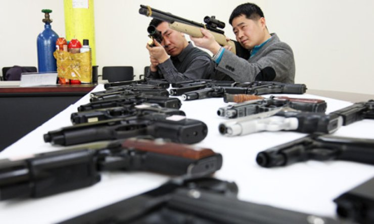 Officers at the Gyeonggi Provincial Police Agency examines guns it confiscated from illegal sellers on the Internet in this file photo taken in February 2012. The nation enforces strict gun control regulations, but it needs to do more to crack down on illegally traded firearms. / Korea Times