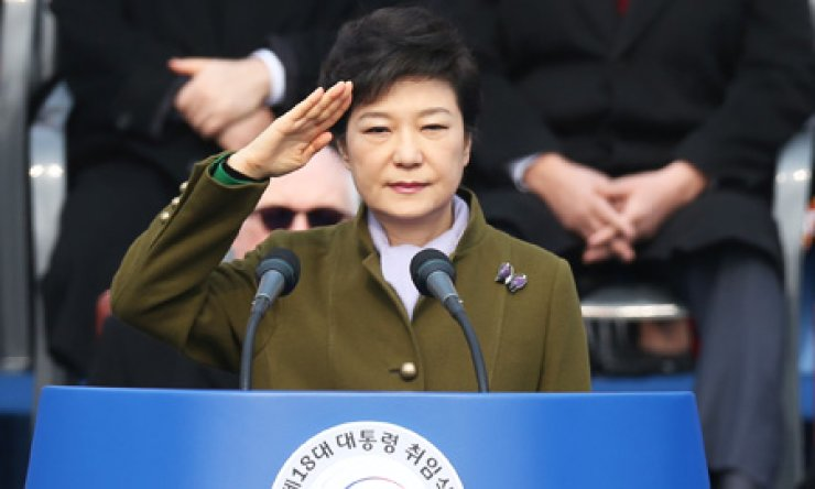 President Park Geun-hye returns a salute to a military honor guard during her swearing-in ceremony at the National Assembly in Yeouido, Monday. At bottom right, Park in traditional clothing walks into the executive building at Cheong Wa Dae. / Yonhap