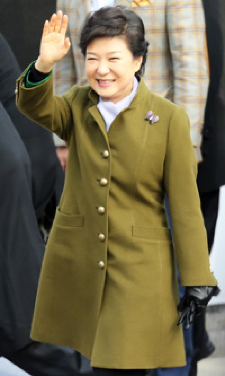 President Park Geun-hye greets the crowd at her inauguration ceremony held Monday outside the National Assembly building in Seoul. Park appeared in a gold-buttoned A-line khaki coat with matching accessories. / Yonhap