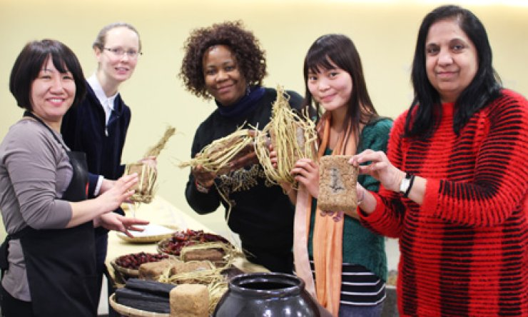 Foreigners hold 'meju' - fermented soy blocks, a key ingredient of 'doenjang' or soybean paste - during a culinary class at the Sempio Foods headquarters in Seoul, Wednesday./ Courtesy of Sempio Foods