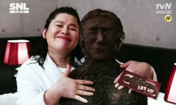 This screen capture shows comedian Lee Young-ja holding a human-shaped 'husband chocolate' on 'Saturday Night Live (SNL) Korea.' / Korea Times