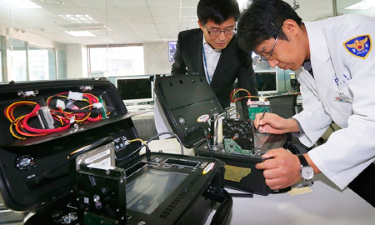Officers from the National Police Agency's Cyber Terror Response Center examine computer hard drives damaged by Wednesday's cyber attack on banks and TV stations at the center's office, Seoul, Thursday. / Yonhap