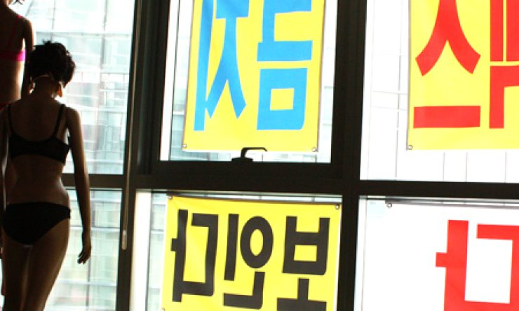 Signs posted on windows of a Hyundai I'Park apartment in Busan, Tuesday, read. 'No sex, we can see all.' A resident of the luxury apartment complex put the signs, warning hotel customers of Park Hyatt Busan that residents can see them due to the short distance between the two buildings. Seen left are mannequins the resident placed alongside the signs.  / Yonhap