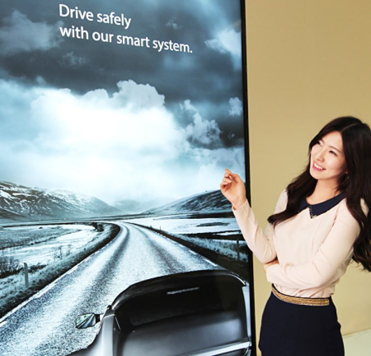 A model poses next to an 84-inch liquid crystal display (LCD) panel that supports ultra high-definition(UHD) viewing, developed by LG Display.                                                                                                     / Courtesy of LG Display