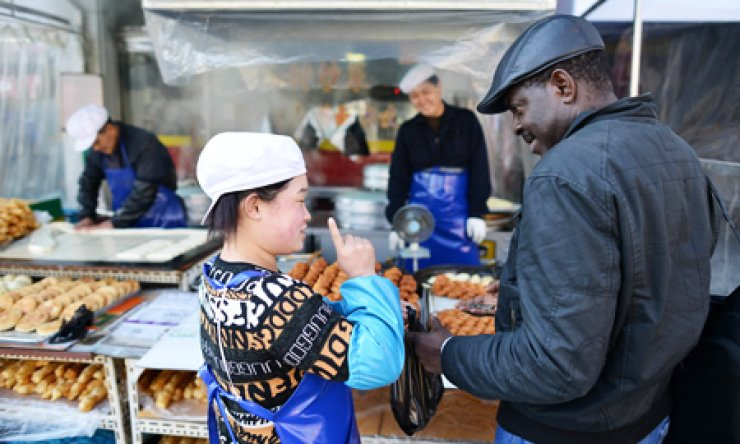 A foreigner purchases donuts at a street bakery run by Chinese immigrants at Wongok-dong, Ansan, Gyeonggi Province.                                                                      / Korea Times photo by Shim Hyun-chul