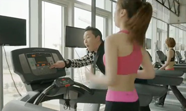 Psy presses a button to speed up a treadmill to cause a woman to fall off it in this video capture from his music video 'Gentleman.'