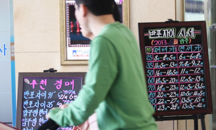 A couple passes by signboards indicating house prices in Gangam-gu, southern Seoul, on May 5. The housing market has shown signs of rebound, with the trading volume picking up following the announcement of the government's stimulus package on April 1. / Yonhap