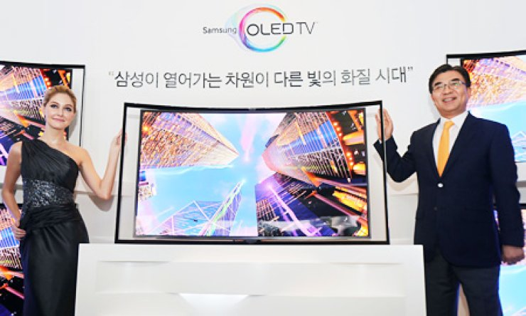 Kim Hyun-seok, right, the head of Samsung Electronics' visual display division, poses next to its 55-inch curved OLED TV during a launch event at the firm's main office in Seocho-dong, southern Seoul, Thursday./ Courtesy of Samsung Electronics