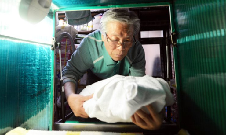 Pastor Lee Jong-rak removes an infant from a 'baby box' attached to a hospice in Gwanak, southwestern Seoul in this April 25 file photo./ Korea Times photo by Shin Sang-soon