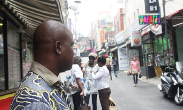 An African man stands outside a restaurant in Itaewon, one of the popular attractions for foreign tourists and migrant workers in Seoul. Many visitors complain that some bars and other entertainment facilities refuse to let foreigners in, inviting criticism for racial discrimination and xenophobia./ Korea Times
