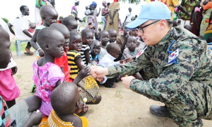 A medic of the Hanbit Unit gives candy to children in the city of Bor, South Sudan in this photo, released by the Joint Chiefs of Staff on Sunday. The 282-member contingent for U.N. peacekeeping operations has been dispatched to the newly-independent African nation to aid reconstruction efforts. / Courtesy of JCS