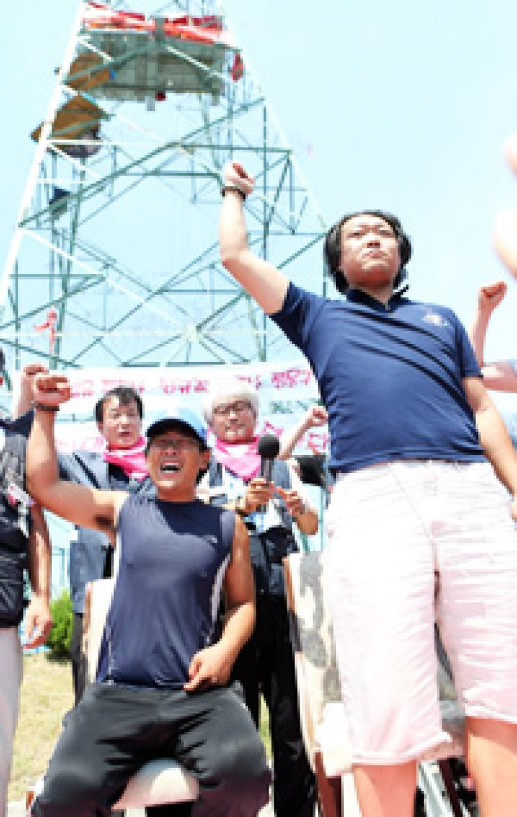 Two former Hyundai Motor non-permanent workers, Chun Eui-bong, left, and Choi Byung-seung, chant a slogan after they came down from a high-rise steel tower near the company's assembly line in Ulsan Thursday, 296 days after they started their protest. / Yonhap