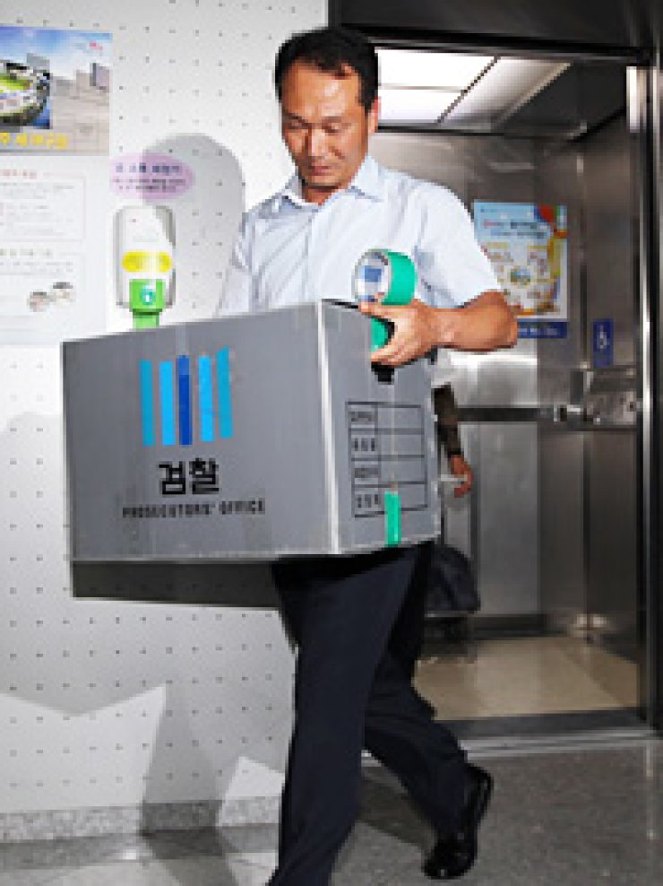 An investigator walks out of Gwangju Mayor Kang Un-tae's office in the southwestern city, carrying a box after a raid there, Thursday. / Yonhap