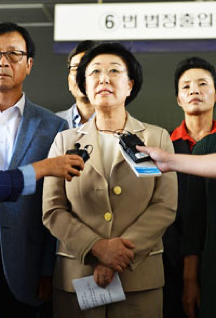 Rep. Han Myeong-sook of the main opposition Democratic Party speaks to reporters at Seoul High Court in Seoul, Monday, after the court sentenced the former Prime Minister to two years in prison and a fine of 883 million won on charges of accepting illegal political funds./ Yonhap