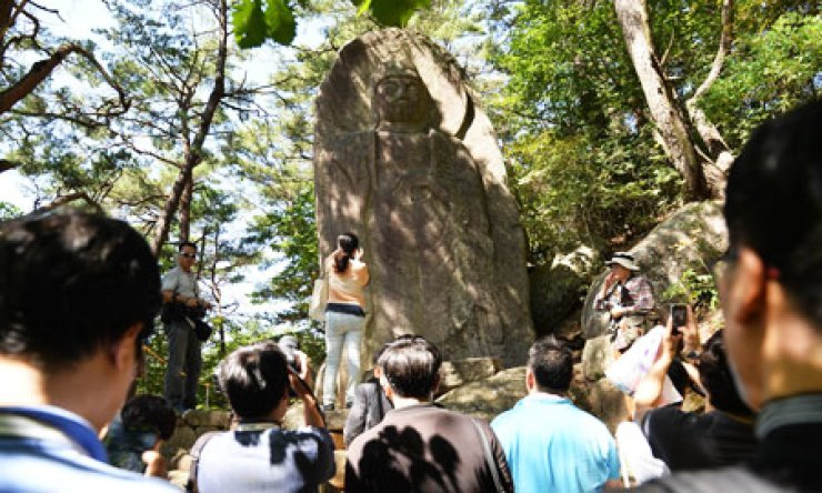 Tourists take photos of the 'Maebul' or the rock-carved standing Buddha at the Haeinsa Temple in Hapcheon, South Gyeongsang Province, Wednesday. The temple unveiled the ninth-century statue prior to the opening of the 2013 Tripitaka Koreana Festival, which kicks off today for 46 days./ Korea Times photo by Shim Hyun-chul