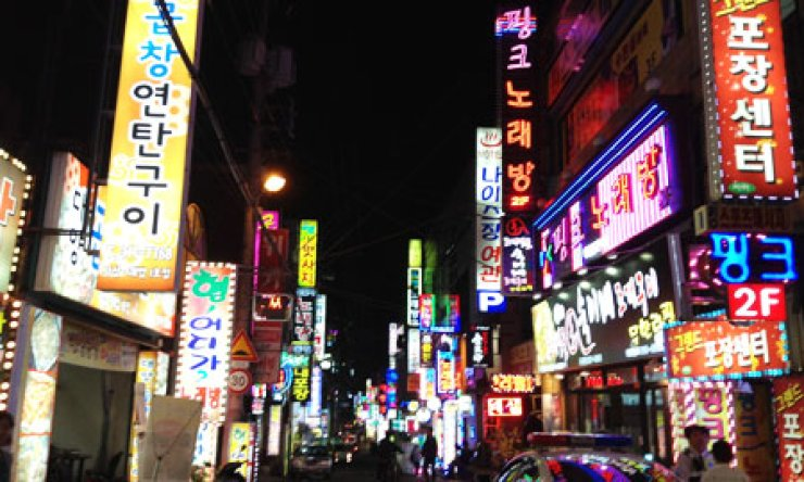 Signs for karaoke bars and other entertainment establishments light a street near Sasang station in downtown Busan./ Korea Times photo by Kim Young-jin