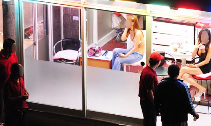 Passersby talk with sex workers in a red-light district in Cheongryang, Seoul in this July, 2011 file photo. / Korea Times