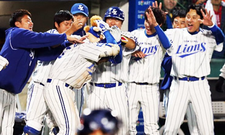 Samsung Lions players congratulate Park Han-yi, third from left, after he hit a three-run home run off Doosan Bears pitcher Dustin Nippert in the seventh inning of their game in Daegu Thursday. / Yonhap