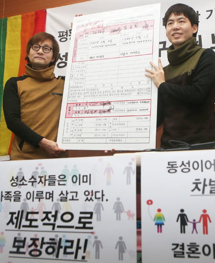 Movie director Kim-Jho Kwang-soo, left, 48, and his partner Kim Seung-hwan hold a blown-up copy of a marriage registration form during a press conference at which they urged the government to recognize their union at the office of the People's Solidarity for Participatory Democracy in central Seoul, Tuesday. They sent their marriage registration form to Seodaemun District Office, but the office said it will not accept it. / Yonhap