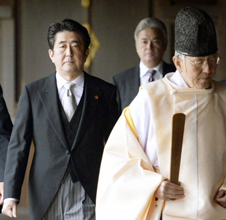 Japan's Prime Minister Shinzo Abe is led by a Shinto priest as he visits the Yasukuni Shrine in Tokyo, Thursday, drawing sharp rebukes from Asian neighbors, South Korea and China. / Yonhap