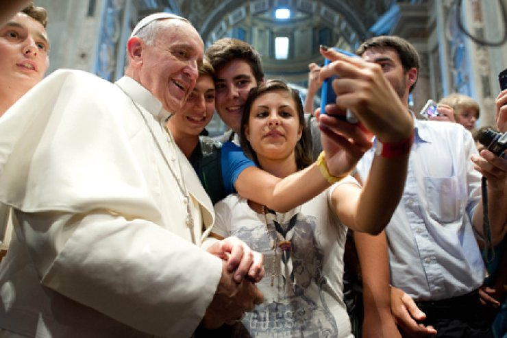 Pope Francis has his picture taken inside St. Peter's Basilica with youths from the Italian Diocese of Piacenza and Bobbio who came to Rome for a pilgrimage, at the Vatican, in August, 2013. / AP-Yonhap