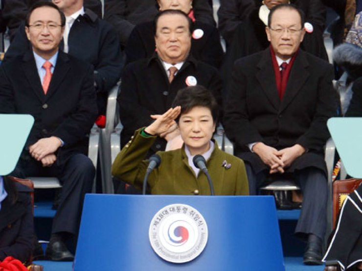 President Park Geun-hye returns a salute to a military honor guard during her swearing-in ceremony at the National Assembly in Yeouido on Feb. 25. Behind her are Saenuri Party Chairman Hwang Woo-yea, right, and then Democratic Party interim leader Moon Hee-sang, center./ Korea Times file