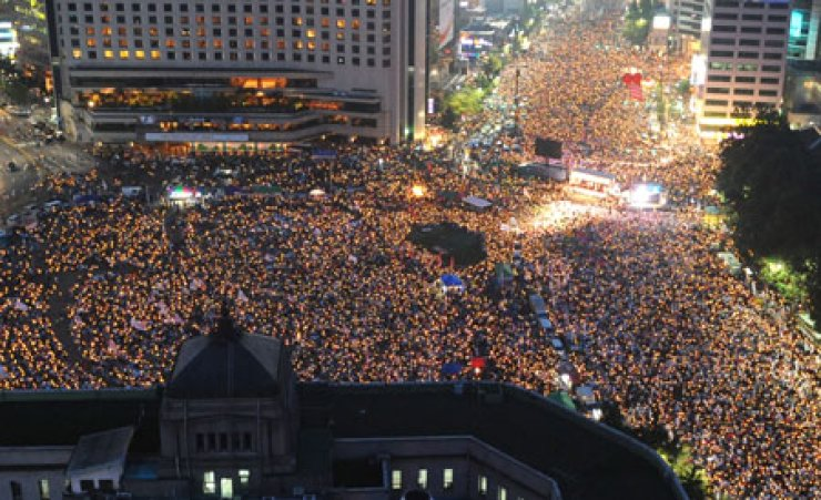 Tens of thousands of people stage a candlelit rally at Seoul Plaza in downtown Seoul on July 5, 2008, asking the government to renegotiate with the U.S.over beef imports. / Korea Times file