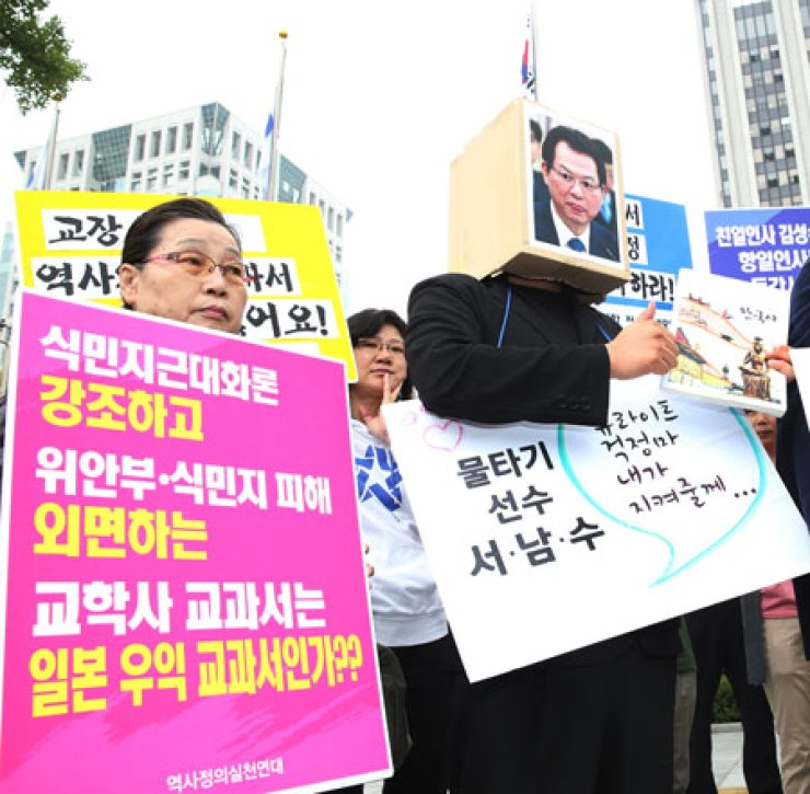Protesters hold banners denouncing Kyohak Publishing Co.'s controversial history textbook during a rally in Seoul, Sept. 12. They called for the retraction of the authorization of the textbook for what they claim is a biased and flawed portrayal of modern Korean history. / Yonhap