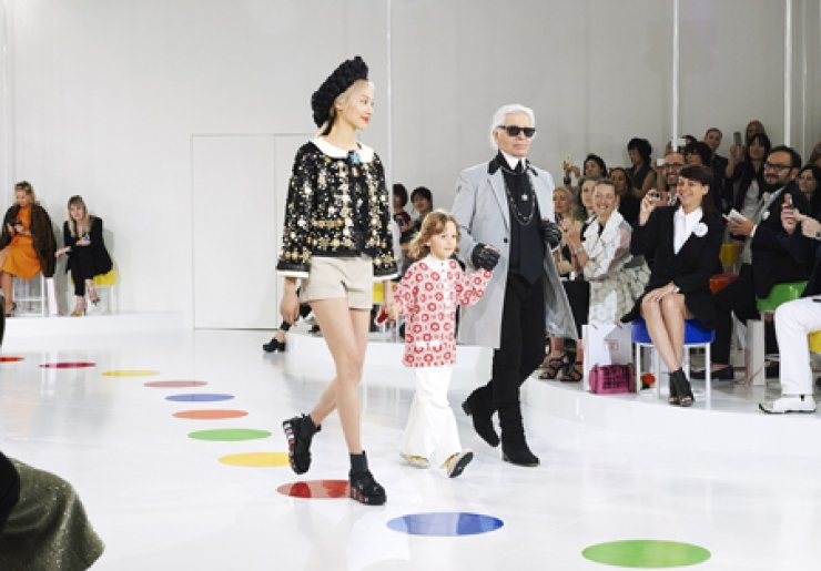 Fashion designer Karl Lagerfeld, right, walks the runway with model Soo Joo and a child after the presentation of his 2015/16 Chanel Cruise collection at the Dongdaemun Design Plaza in Seoul, Monday. / Courtesy of Chanel