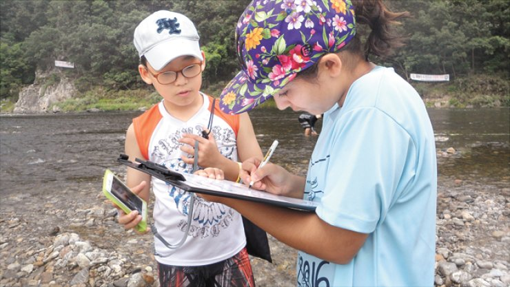 A seventh grade student of Korea International School (KIS) writes down the results of a water test sheand her classmate conducted along the Hongcheon River in Hongcheong, Gangwon Province, Sept. 2.This activity was part of the school's special outdoor Experiential Education (EE) program.  / Courtesy of KIS