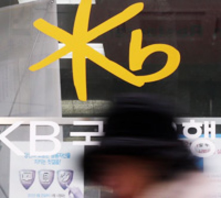 A person walks past a KB Kookmin Bank branch in Seoul, Monday. / Yonhap