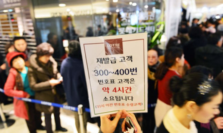 Clients queue in a long line to obtain reissued cards or have their existing cards revoked at the Lotte Card Center in the Lotte Department Store in Myeong-dong, central Seoul, Tuesday. A note reads: 'Customers with waiting numbers from 300 to 400 will have to wait about 4 hours.'/ Korea Times photo by Shim Hyun-chul