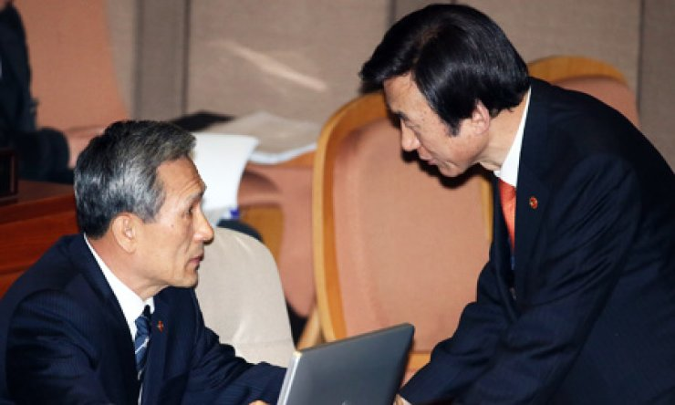 Defense Minister Kim Kwan-jin, left, talks to Foreign Minister Yun Byung-se before attending a parliamentary audit of ministries at the National Assembly, Monday. / Yonhap
