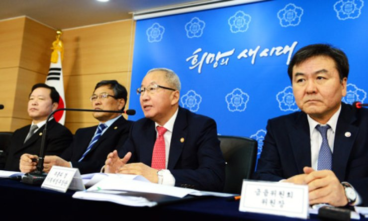 Finance Minister Hyun Oh-seok, center, speaks to the media about the government's personal information protection measures at the government complex in central Seoul, Monday. At right is Financial Services Commission Chairman Shin Je-yoon. / Yonhap