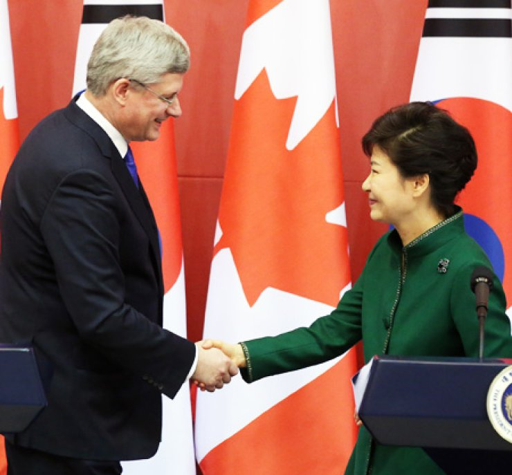 President Park Geun-hye shakes hands with Canadian Prime Minister Stephen Harper during a news conference at Cheong Wa Dae, Tuesday, after signing a free trade agreement. / Yonhap