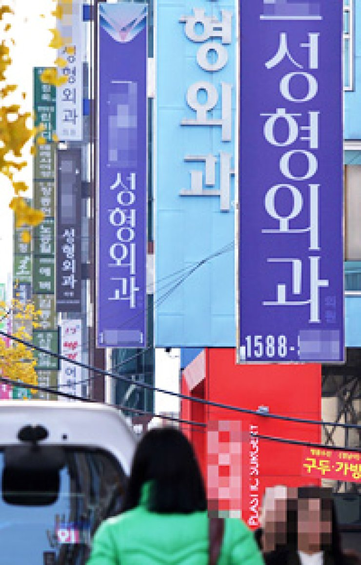 People walk down a street lined with cosmetic surgery clinics in Apgujeong-dong in Seoul. The clinics shown in the photo are not related to this article./ Korea Times file