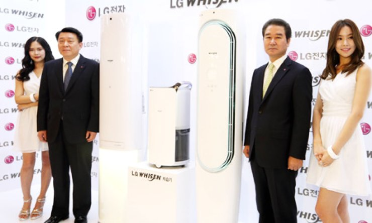 Nho Hwan-yong, second from left, president of LG Electronics' air-conditioning division, and the company's marketing chief Choi Sang-kyu, third from left, stand next to its new air conditioners during a launch event in downtown Seoul, Tuesday. / Courtesy of LG Electronics