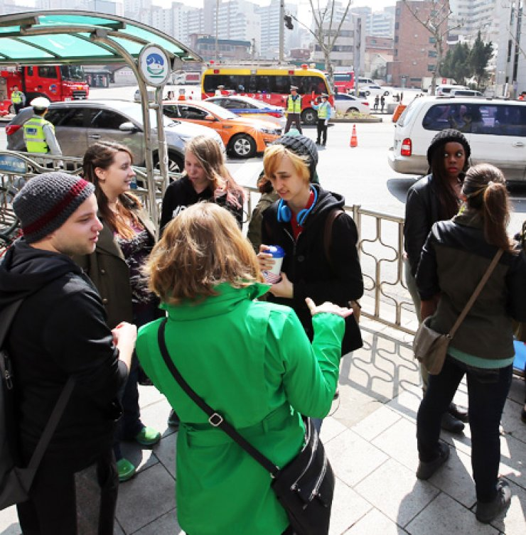 Foreigners gather and chat in the northern part of Mapo District in Seoul, Sunday amid police blocking Mapo Bridge-bound vehicles during the shooting of scenes for blockbuster 'The Avengers: Age of Ultron.' / Yonhap