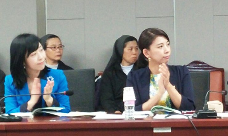 Rep. Jasmine Lee, right, of the ruling Saenuri Party applauds while participants are introduced during a public hearing on a bill to protect undocumented foreign children at the National Assembly Members' Office building in Seoul, Thursday. / Korea Times photo by Jun Ji-hye