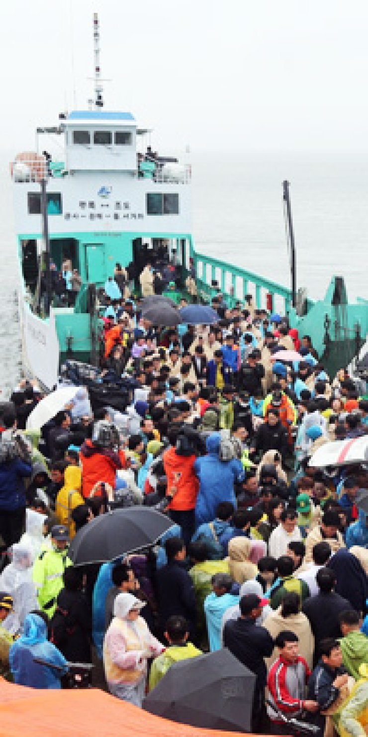 Some 200 relatives of passengers missing from the sunken ferry, Sewol, disembark at Jindo, South Jeolla Province, Thursday, after inspecting the accident scene./ Yonhap